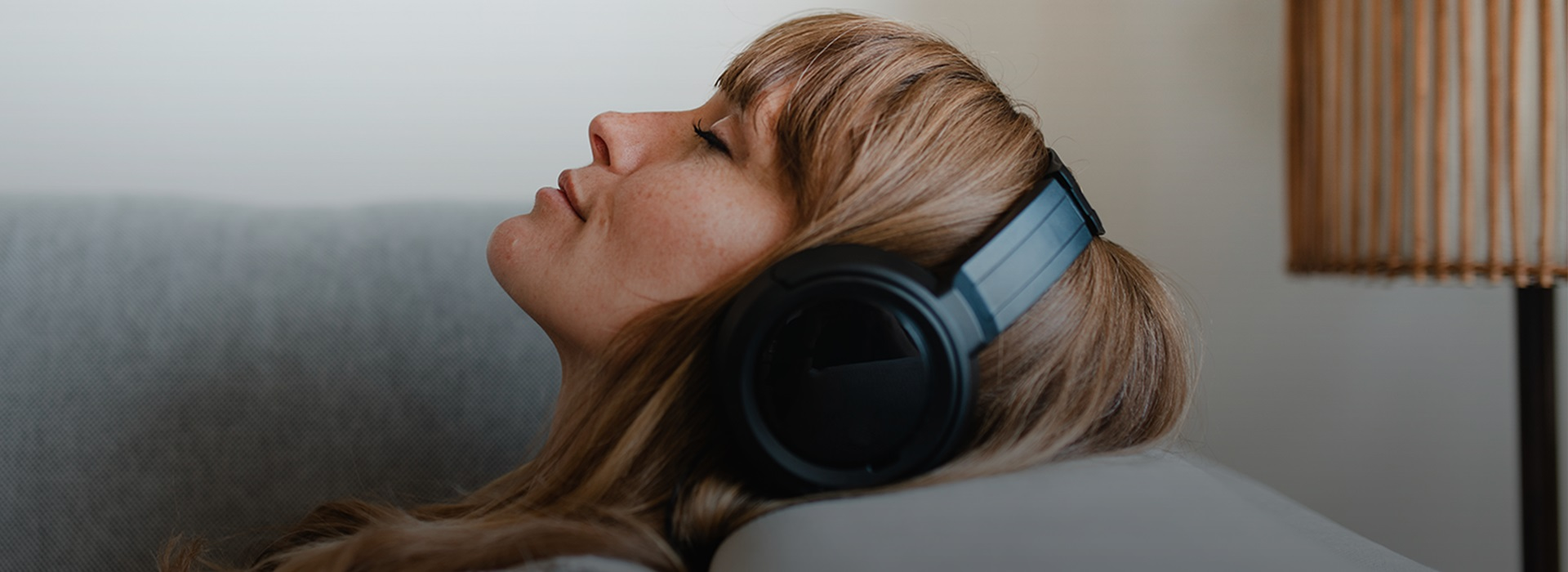A woman is lying on the couch and listening to music on headphones