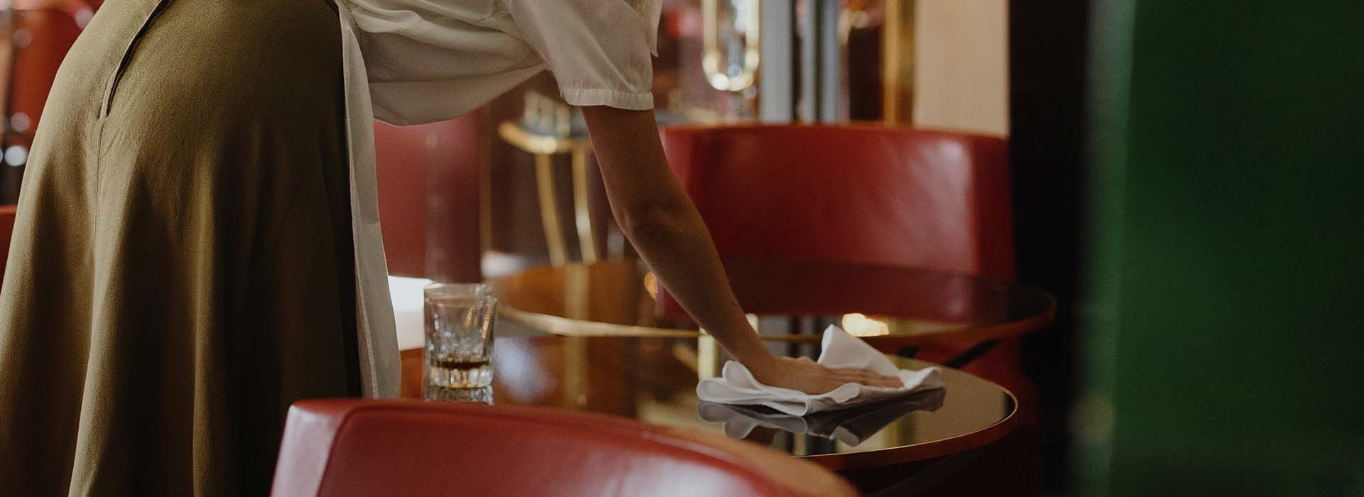 Female waiter cleaning bar table